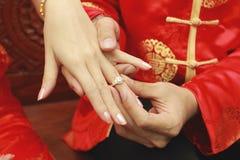 Cerimonia di impegno, anello vicino su sul fondo tradizionale cinese del panno fotografia stock libera da diritti