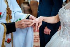 Cerimonia di nozze in anelli di oro della chiesa sul dito fotografia stock libera da diritti