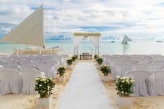 Cerimonia di nozze su una spiaggia tropicale nel bianco L'arco è decorazione fotografia stock libera da diritti