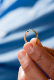 Cerimonia nuziale dell'oro della holding della mano Fascia-Verticale immagine stock