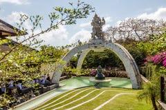 Cerimonie a Pura Luhur Uluwatu, indù di balinese che si siede in una balla vicino alla statua di una scimmia Bali, Indonesia Fotografia Stock