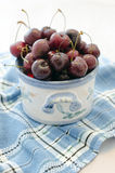 Cerise. Cherries in a bowl earthenware on blue tablecloth Royalty Free Stock Photo