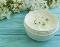 Cerise de floraison saine de crème hydratante de traitement organique cosmétique crème de produit sur une protection en bois bleu Image stock