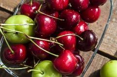 Cerise et prunes vertes dans le plat de regard merveilleux, cerise et prunes en fruit d'été les peintures de cerise les plus merv Photo libre de droits