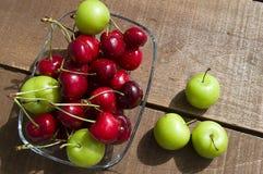Cerise et prunes vertes dans le plat de regard merveilleux, cerise et prunes en fruit d'été les peintures de cerise les plus merv Images libres de droits