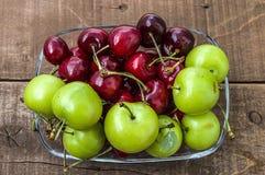 Cerise et prunes vertes dans le plat de regard merveilleux, cerise et prunes en fruit d'été les peintures de cerise les plus merv Photo stock