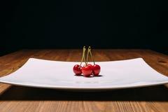 Cerise fraîche de plat sur le fond bleu en bois Cerises mûres fraîches Cerises une de la plaque blanche Images libres de droits