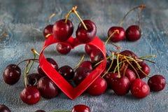 Cerise fraîche ou merise avec des baisses de l'eau avec un coeur rouge Concept pour le jour de valentines photo stock
