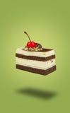 Cerise rayée d'isolement de chocolat cakeflying sur le fond vert Images stock