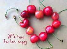 Cerise rouge dans la forme du coeur de tige d'isolement sur le gris avec le texte il est temps d'être heureux Carte de motivation Image stock