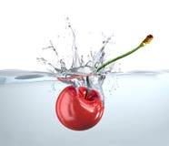 Cerise rouge tombant dans l'eau et l'éclaboussement. Photographie stock