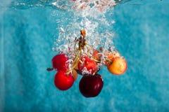 Cerises éclaboussant dans l'eau Image libre de droits