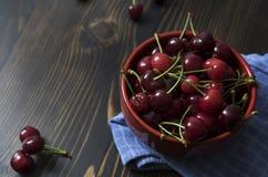 Cerises Cerise Cerises dans la cuvette de couleur et la serviette de cuisine Photographie stock