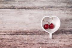 Cerises Chili et tasse en forme de coeur sur en bois Photo libre de droits