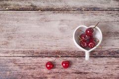 Cerises Chili et tasse en forme de coeur sur en bois Photographie stock