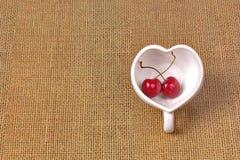 Cerises Chili et tasse en forme de coeur sur la toile à sac Photographie stock