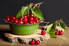 Cerises dans un plat sur la table en bois Image libre de droits