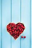 Cerises dans une boîte de coeur sur la table en bois bleue Image libre de droits