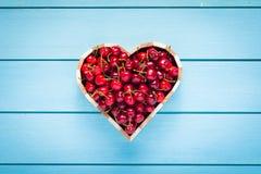 Cerises dans une boîte de coeur sur la table en bois bleue Photo stock