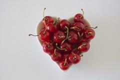 Cerises dans une cuvette en forme de coeur Photo stock