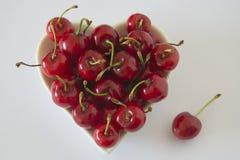 Cerises dans une cuvette en forme de coeur Photo libre de droits