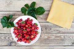 Cerises fraîches et fraises mûres rouges d'un plat blanc Photos stock