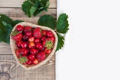Cerises fraîches et fraises mûres rouges d'un plat blanc Photos libres de droits
