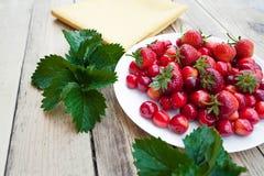 Cerises fraîches et fraises mûres rouges d'un plat blanc Images stock