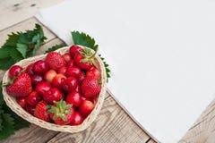 Cerises fraîches et fraises mûres rouges d'un plat blanc Image libre de droits