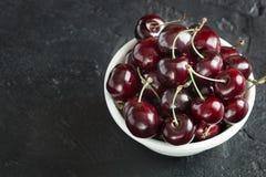 Cerises fraîches mûres dans un plat blanc Image stock