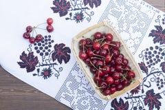 Cerises fraîches sur la serviette brodée Image stock