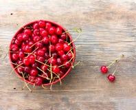 Cerises mûres rouges avec des queues dans un plat circulaire sur le vieux fond en bois photos stock