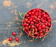 Cerises mûres rouges avec des queues dans un plat circulaire sur un vieux fond en bois noir avec une fente Photo stock