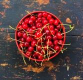 Cerises mûres rouges avec des queues dans un plat circulaire sur un vieux fond en bois noir avec une fente image stock