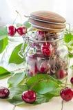 Cerises marron mûres dans un vase en verre et un pot Photographie stock