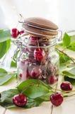 Cerises marron mûres dans un vase en verre et un pot Photos libres de droits