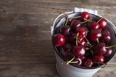 Cerises rouges dans le seau blanc sur la table en bois Consommation saine de récolte de ressort Fruits Photos stock