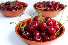 Cerises rouges mûres dans cuvettes en bois d'isolement sur le fond blanc Images stock