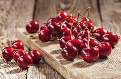 Cerises rouges mûres sur de vieux conseils image stock