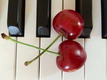 Cerises rouges sur le piano Image libre de droits