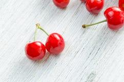 Cerises sur un fond blanc Baies rouges avec les brindilles vertes Photographie stock