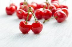 Cerises sur un fond blanc Baies rouges avec les brindilles vertes Photographie stock libre de droits