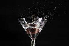 Cerises tombant dans l'eau, éclaboussant le verre de vin Photos libres de droits