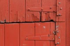 Cerniere di porta sulla vecchia porta di legno rossa rustica immagini stock