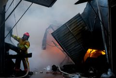 Cernivci/Ucraina - 03/19/2018: Pompieri su fuoco Il vigile del fuoco estingue il fuoco con acqua Il mercato estero è su fuoco fotografia stock