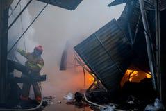 Cernivci/Ucraina - 03/19/2018: Pompieri su fuoco Il vigile del fuoco estingue il fuoco con acqua Il mercato estero è su fuoco fotografia stock libera da diritti
