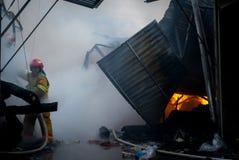 Cernivci/Ucraina - 03/19/2018: Pompieri su fuoco Il vigile del fuoco estingue il fuoco con acqua Il mercato estero è sopra fotografie stock libere da diritti