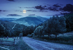 Cerque cerca del camino abajo de la colina con el bosque en montañas en la noche Fotografía de archivo