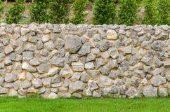 Cerque la superficie real de la pared de piedra con el cemento en campo de hierba verde Imagen de archivo libre de regalías