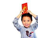 Cerrado encima de niño asiático sonriente está llevando a cabo los paquetes rojos y palabra china todo el beneficio del significa Imágenes de archivo libres de regalías
